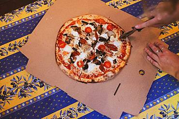 High angle close up of person cutting pizza with a pizza wheel