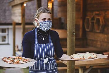 Woman waitress in apron and face mask holding plate of pizza