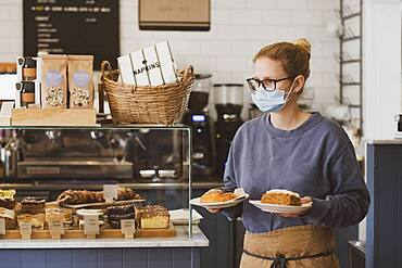 Waitress wearing face mask working in a cafe, carrying plates of food