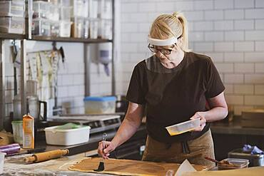 Waitress wearing face mask working in a cafe, preparing food