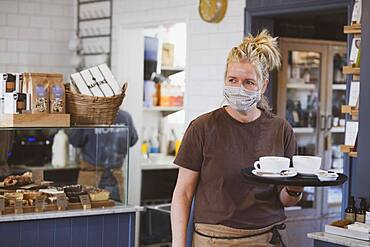 Waitress wearing face mask working in a cafe, carrying tray with coffee cups