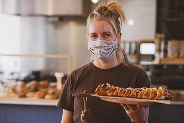Waitress wearing face mask working in a cafe, carrying plate of food