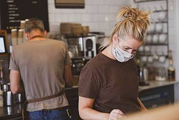 Waitress wearing face mask working in a cafe