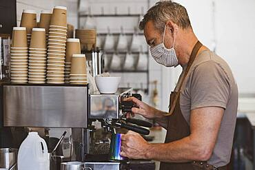 Male barista wearing brown apron and face mask working in a cafe, making espresso