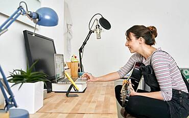 Woman using laptop for teaching guitar online