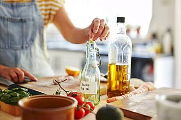 Woman putting garlic into bottle of olive oil in kitchen