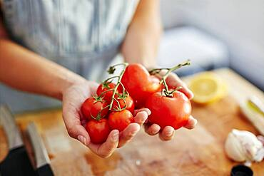 Woman holding different sized organic tomatoes in kitchen