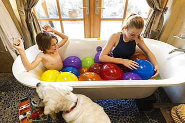 Young boy and his older sister in bathtub filled with water balloons