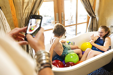 Person taking a smart phone photograph of a young boy and his older sister in bathtub with water balloons