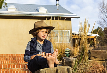 Portrait of young boy wearing fedora hat relaxing on his porch
