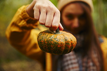 Woman holding up pumpkin to camera