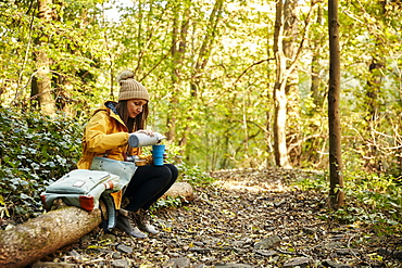 Woman sitting on tree trunk in woodland pouring drink from thermos flask