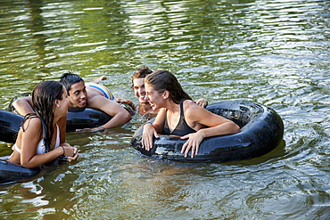 A group of young people, boys and girls, swimming and floating using swim floats and inflated tyres, Maryland, USA