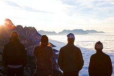 Group of young men watching the sunrise above the clouds, Trentino-Alto Adige, South Tyrol in Bolzano district, Alta Pusteria, Hochpustertal,Sexten Dolomites, Italy