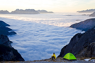 Man and tent above the clouds, Trentino-Alto Adige, South Tyrol in Bolzano district, Alta Pusteria, Hochpustertal,Sexten Dolomites, Italy