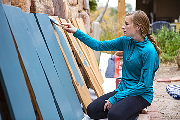 Teenage girl painting wooden shelves blue
