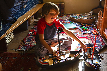 Overhead view of young boy in his room playing with his toys