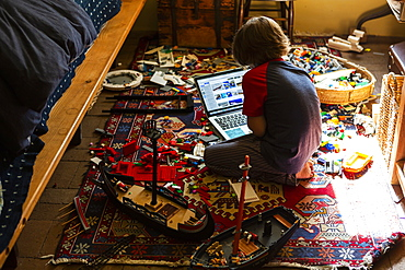 Young boy playing in his room, looking at laptop
