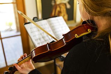 Teenage girl practicing violin at home