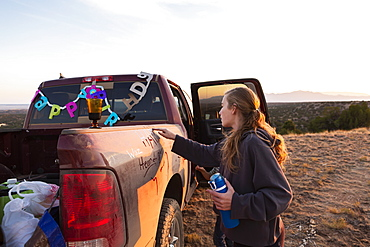 Teenage girl writing on the panel of an old pickup truck