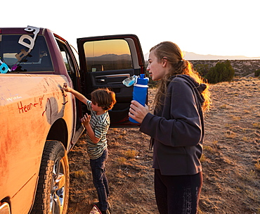 Two children painting the side of an old pickup truck