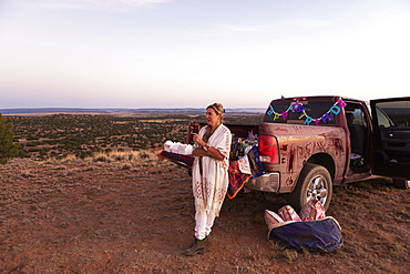 adult woman leaning on pickup truck at sunset, Galisteo Basin