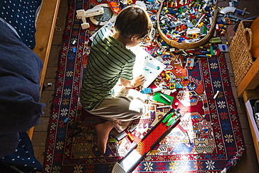 Boy sitting among toys on his bedroom floor in a patch of sunlight