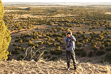 young boy in Galisteo Basin looking through binoculars at sunset
