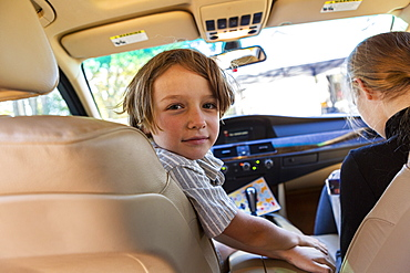 Young boy looking at camera in parked car