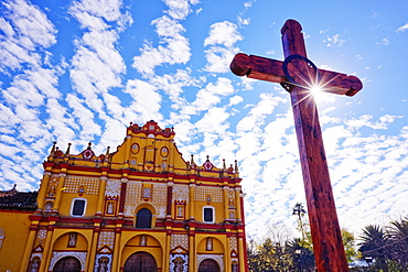 Crucifix in a courtyard in front of an ornate painted church