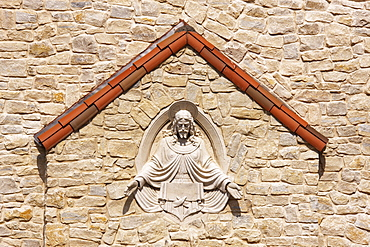Sculpture of Jesus set into stone wall