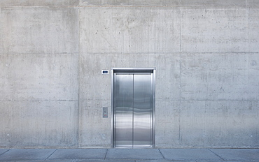 Metal elevator doors in a concrete wall