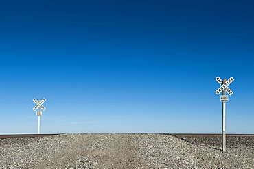 Railway crossing signs in desert landscape