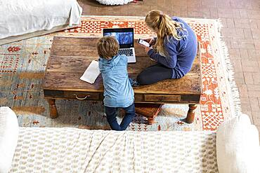 overhead view of teenage girl and her younger brother using laptop and smart phone
