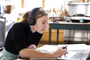 teenage girl wearing headphones, drawing on paper