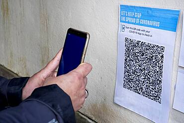Close-up of person with smartphone scanning QR code in conjunction with the Covid-19 app.