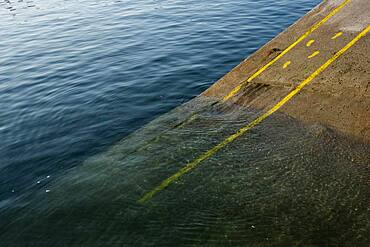 High angle close up of yellow footprints and lines painted on asphalt ground in a harbour.
