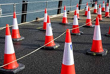 Close up of large number of traffic cones lined up on a harbour wall.