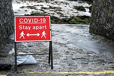 Red and white Covid-19 distancing sign.