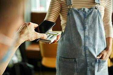 Woman wearing face mask holding contactless payment device, customer paying using a mobile phone