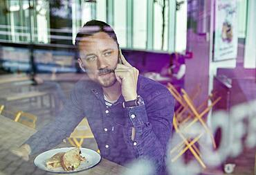 Man in a face mask seated at a cafe table using a mobile phone, view through a window