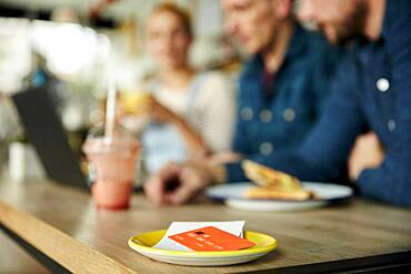 People at a cafe table, a saucer with till receipt and credit card.