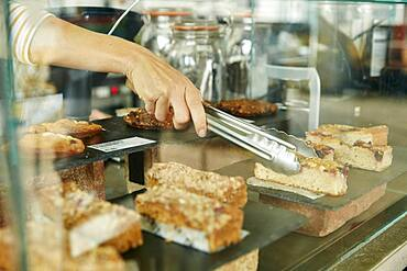 Close up of tongs selecting a slice of cake in cafe