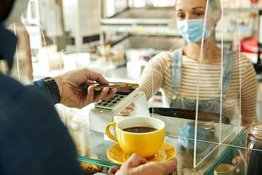 Woman in a face mask behind cafe safety screen, offering a contactless payment terminal to customer