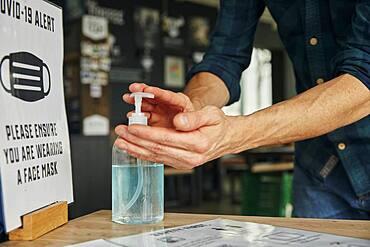 Man using hand sanitiser gel in restaurant