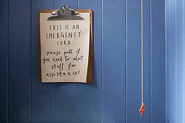 Close up of clipboard with emergency cord instructions on blue wall.