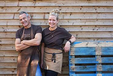 Man and woman in aprons, colleagues taking a break from work, laughing