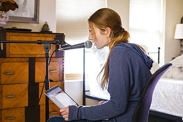 Teenage girl singing into a microphone in her bedroom