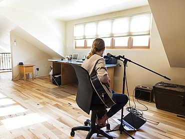 Fourteen year old teenage girl playing her guitar and singing at home in loft space