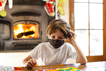 Young boy wearing mask playing board game alone at home